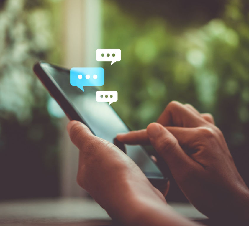 Women hand using smartphone typing, chatting conversation in chat box icons pop up. Social media maketing concept.